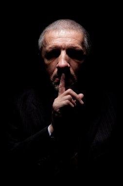 Scary man gesturing silence