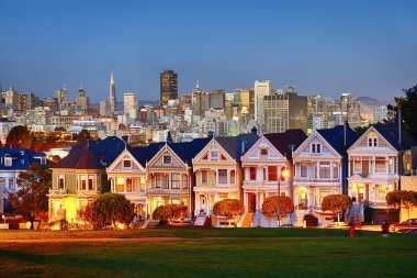 The Painted Ladies of San Francisco, California sit glowing amid the backdrop of a sunset and skyscrapers. stock vector