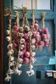 Fotografia cipolla rossa e aglio poggiate sulla vecchia porta