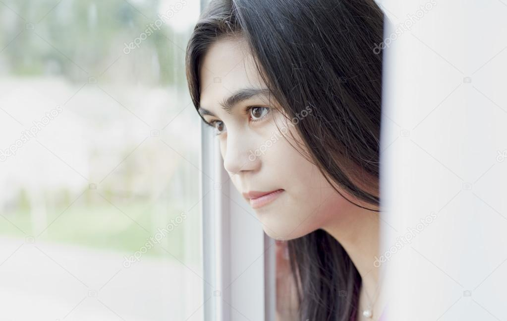 Side profile of teen girl or young woman looking out window ...