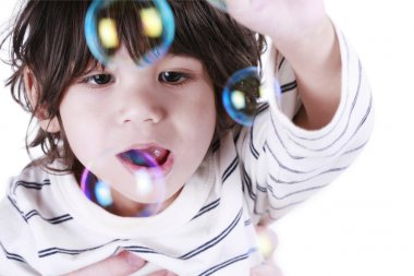 Toddler boy playing with bubbles