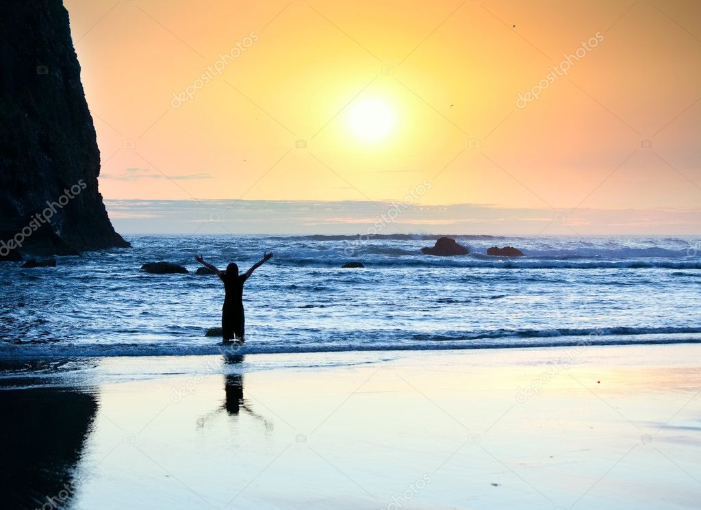 Girl standing in waves, arms raised to sky at sunset