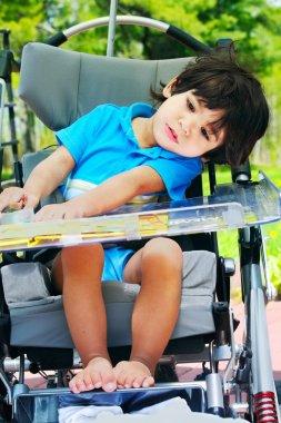 Disabled child in medical stroller