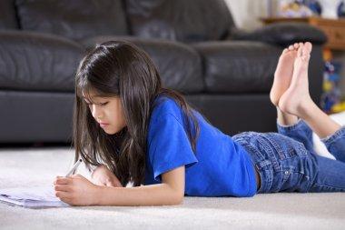 Little girl doing her homework on floor