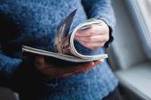člověk se dívá na časopis. stisknutím rukou.