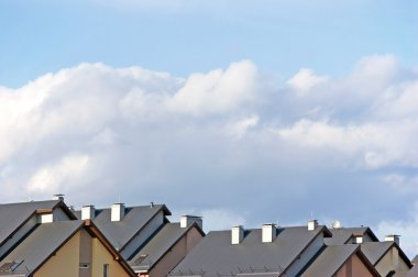 Row house roofs, condo rooftop panorama and bright summer cloudscape