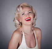 Fotografie hezká blondýnka modelu jako marilyn monroe v bílých šatech s červenými rty na šedém pozadí