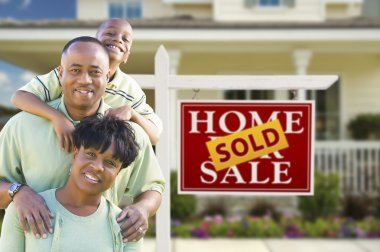 African American Family In Front of Real Estate Sign and House