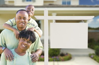 African American Family In Front of Blank Real Estate Sign and House