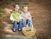 Two Children on Wood Steps with Basket of Pine Cones