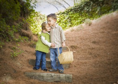Two Children with Basket Hugging Outside on Steps