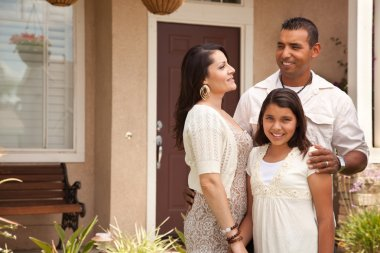 Small Happy Hispanic Family in Front of Their Home