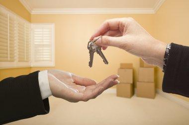Woman Handing Over the House Keys Inside Empty Room