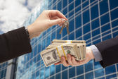 Fotografie Handing Stack of Cash For Key and Corporate Building