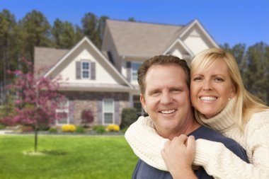 Happy Couple Hugging in Front of House