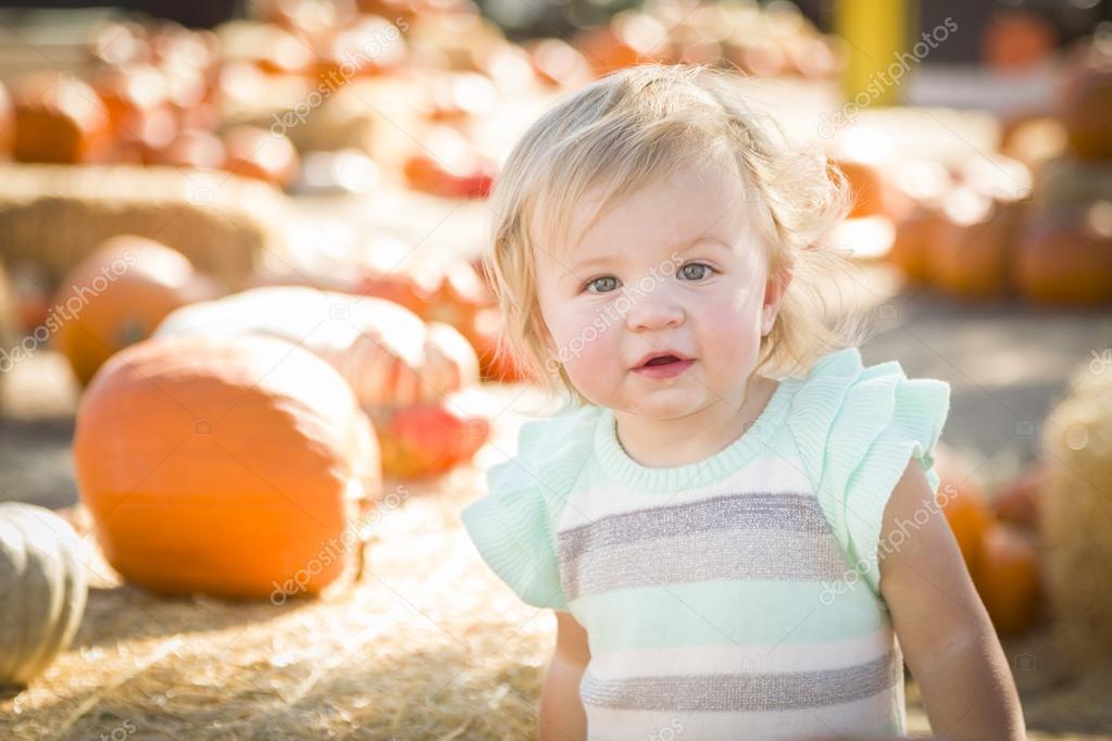 Adorable Baby Girl Having Fun at the Pumpkin Patc