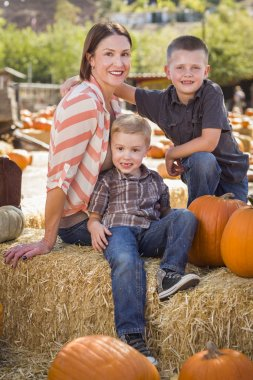 Portrait of Attractive Mother and Her Sons at Pumpkin Patc