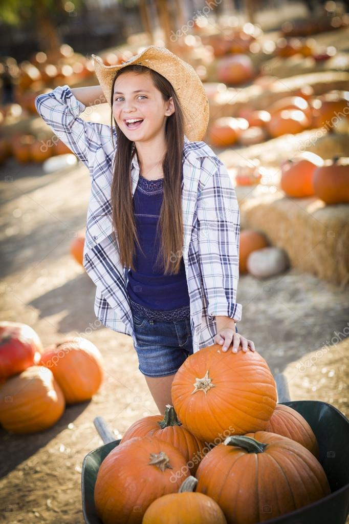 583bdb482f7 Preteen Girl Wearing Cowboy Hat Playing with a Wheelbarrow at the Pumpkin  Patch in a Rustic Country Setting — Photo by Feverpitch