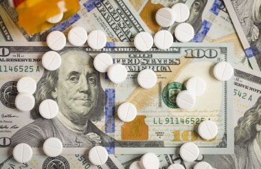 Medicine Pills Scattered on Newly Designed U.S. One Hundred Dollar Bills. stock vector