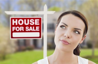 Thinking Woman In Front of House and For Sale Sign