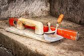 Fotografia cazzuole e altri strumenti di muratura su un muro di cemento