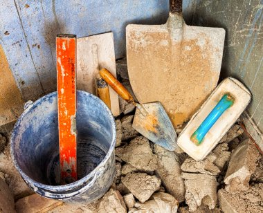 Masonry tools in the corner of an unfinished concrete wall