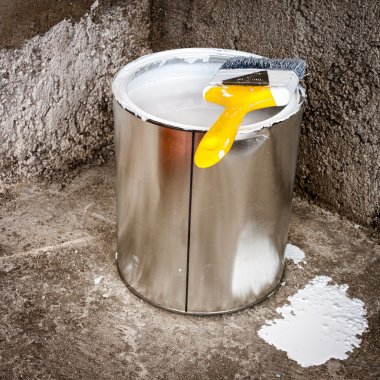 Metallic can of white paint over rough concrete
