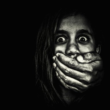 Frightened girl being silenced by an adult hand isolated on blac