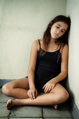 Girl with a sad expression sitting in a corner