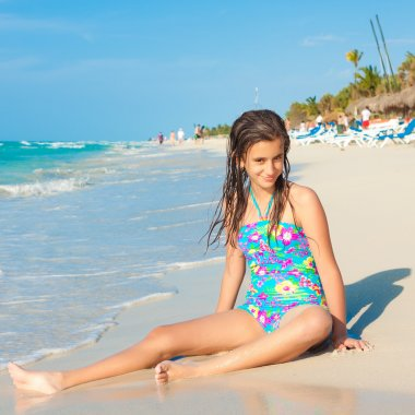 Cute hispanic teen sitting on a sunny beach