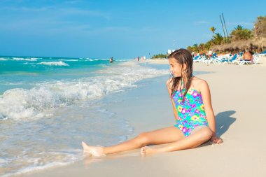 Cute hispanic teen sitting on a sunny beach in Cuba