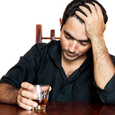Hispanic man holding an alcoholic drink and suffering a headache
