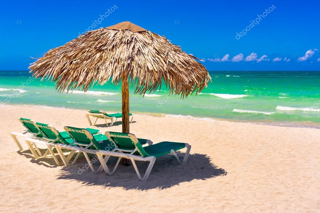 Thatched umbrellas and beach beds on a cuban beach