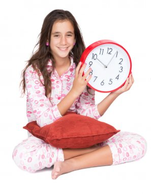 Girl wearing pajamas and holding a clock