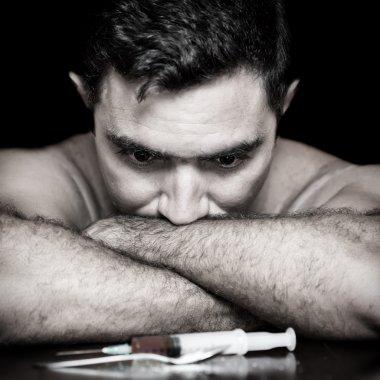 Depressed drug addict and a syringe