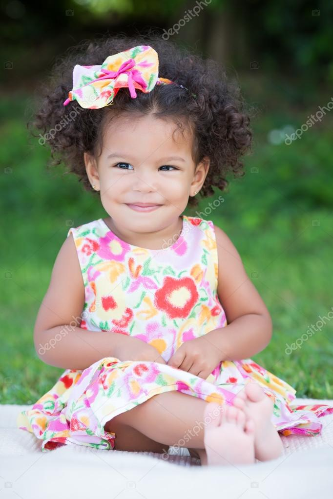 Small Girl With An Afro Hairstyle Sitting On The Grass Stock Photo