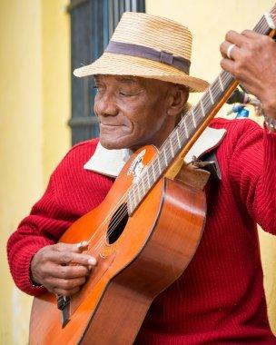 Old afrocuban street musician playing the guitar in Havana
