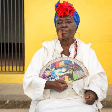 Old black lady smoking a cuban cigar in Havana