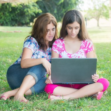 Hispanic girl and her young mother using a laptop computer outdoors stock vector