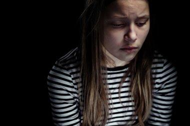 Dark portrait of a crying teen girl, studio shot