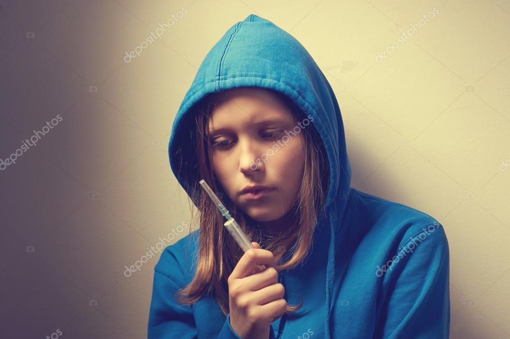 Dark portrait of a junk teen girl with syringe