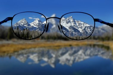 Glasses with clear vision of Teton Mountains in background stock vector