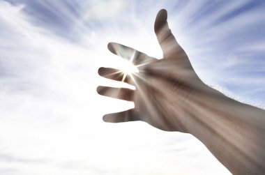 Person's Hand Reaching Towards Heaven Sunlight
