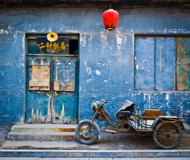 Motorbike cart parked in front of the decaying blue facade of an abandoned shop in Pingyao, China stock vector