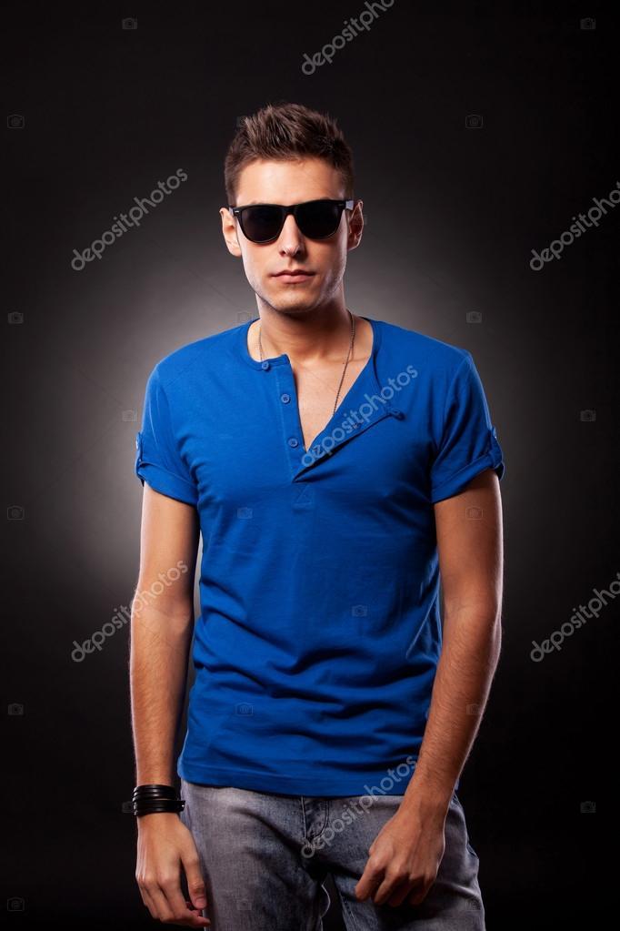 4a18a051479270 Modèle de jeune homme vêtu de bleu t-shirt et lunettes de soleil– images de  stock libres de droits