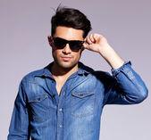 Fotografia uomo che tiene i suoi occhiali da sole alla moda