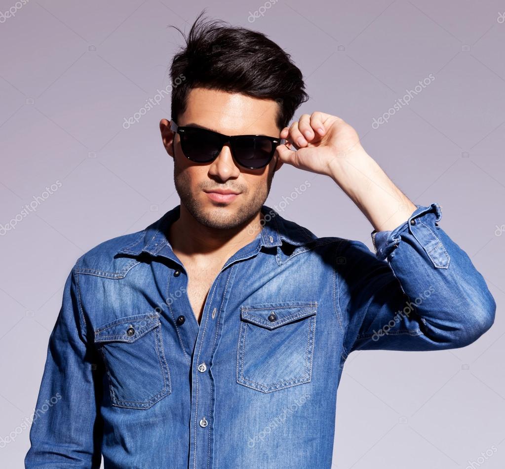 man holding his fashionable sunglasses