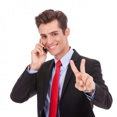 business man making victory sign while talking on phone