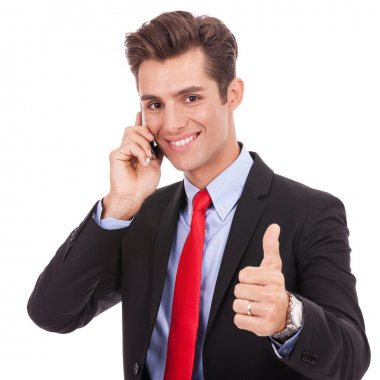 business man talking on the smart phone and making ok