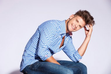 Fashion male model sitting and laughing